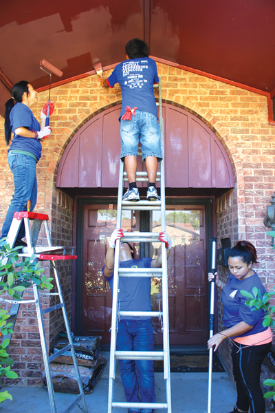 Members of the Rotaract Club paint and do yard work on a homeowner's property. The Rotaract Club and Phi Theta Kappa brought 12 students each, helping make up about 1,000 volunteers who participated on Addressing Mesquite Day. PHOTO BY ANDREA CARRIZALES/THE ET CETERA