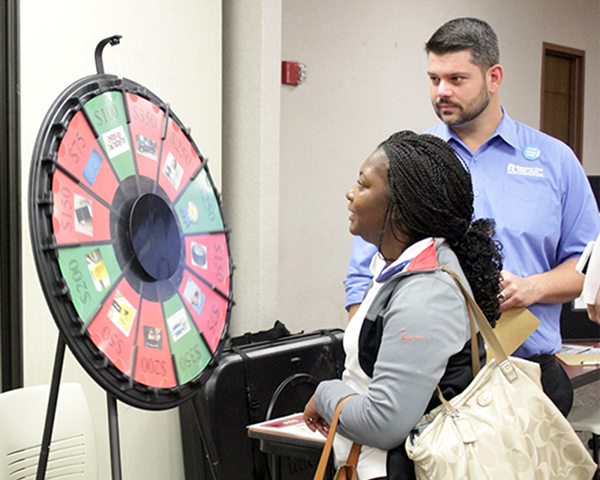 """Teresha Richardson spins the """"Wheel of Misfortune"""" at the Reality Fair. At the end of the course, the wheel simulated life's unplanned events. GUILLERMO MARTINEZ/THE ET CETERA"""