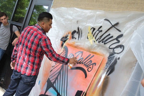Arturo Donjuan spray-painting a piece of lauan wood April 21. PHOTO BY JASMIN JIMENEZ/THE ET CETERA.