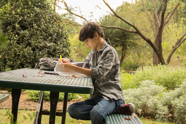 Matthew Espinosa, a 15-year-old dual credit student at Eastfield College, studies for his history class at the arboretum. Espinosa's mother, Ruthie Espinosa, homeschools her three children still in school. Photo by James Hartley/The Et Cetera