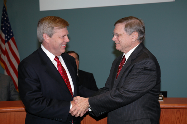 Jerry Prater (right), chair of the DCCCD board of trustees, welcomes Dr. Joe May as the district's seventh chancellor following the trustees' Dec. 3 meeting.