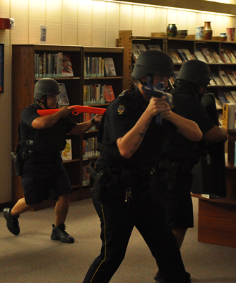 GUILLERMO MARTINEZ/THE ET CETERA Officers Philip Wilburn, John Lozano and Sgt. Kevin Levingston secure the library in a lockdown drill.