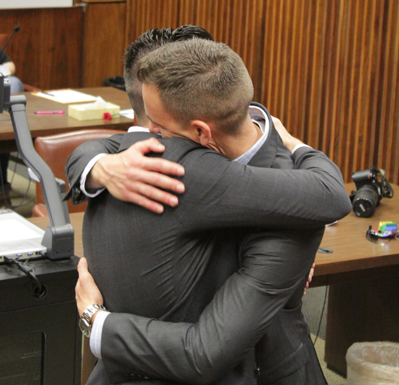 David Telfer, left, and Sean Williamson embrace after their marriage Friday at the George Allen Sr. Courts Building in Dallas. (Photo by James Hartley/The Et Cetera)