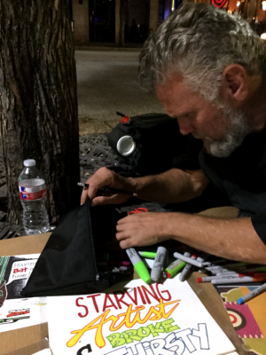 Foster looks through a bag of Sharpie markers and pens provided by Art from the Streets.
