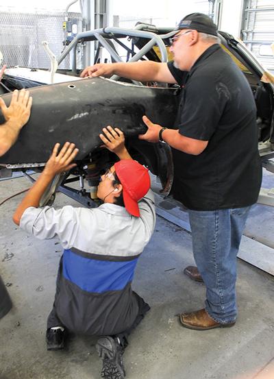 Pedraza and Salazar fit the quarter panel back onto the Miata. PHOTO BY ALEJANDRA ROSAS/THE ET CETERA