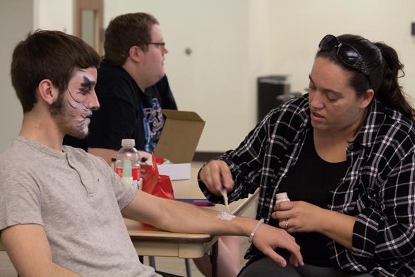 Drama teacher demonstrates theater makeup skills
