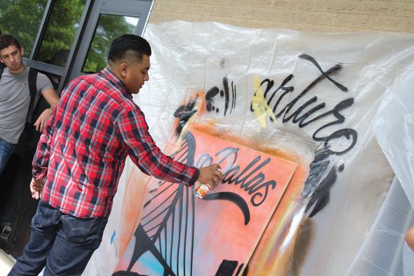 Arturo Donjuan spray-painting a piece of lauan wood April 21. PHOTO BY JASMIN JIMENEZ/THE ET CETERA.