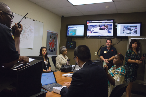 Police and college administrators watch the lockdown drill from the police station. Photo by David Sanchez/The Et Cetera