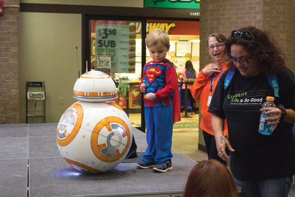 A BB-8 robot built by professor David Kirk takes meets 3-year-old Jake Traynham, grandson of Upward Bounds Sandy Hampton. Photo by Jonathan Wences/The Et Cetera