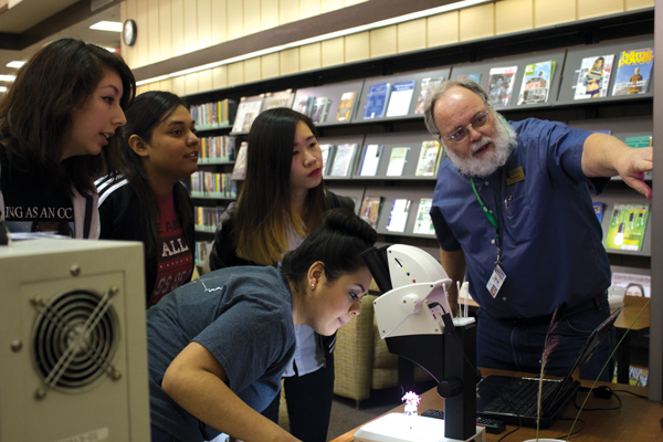 Lab coordinator Murry Gans shows students various microscopes during his Nov. 9 common book event. Photo by Andrew Gonzales/The Et Cetera