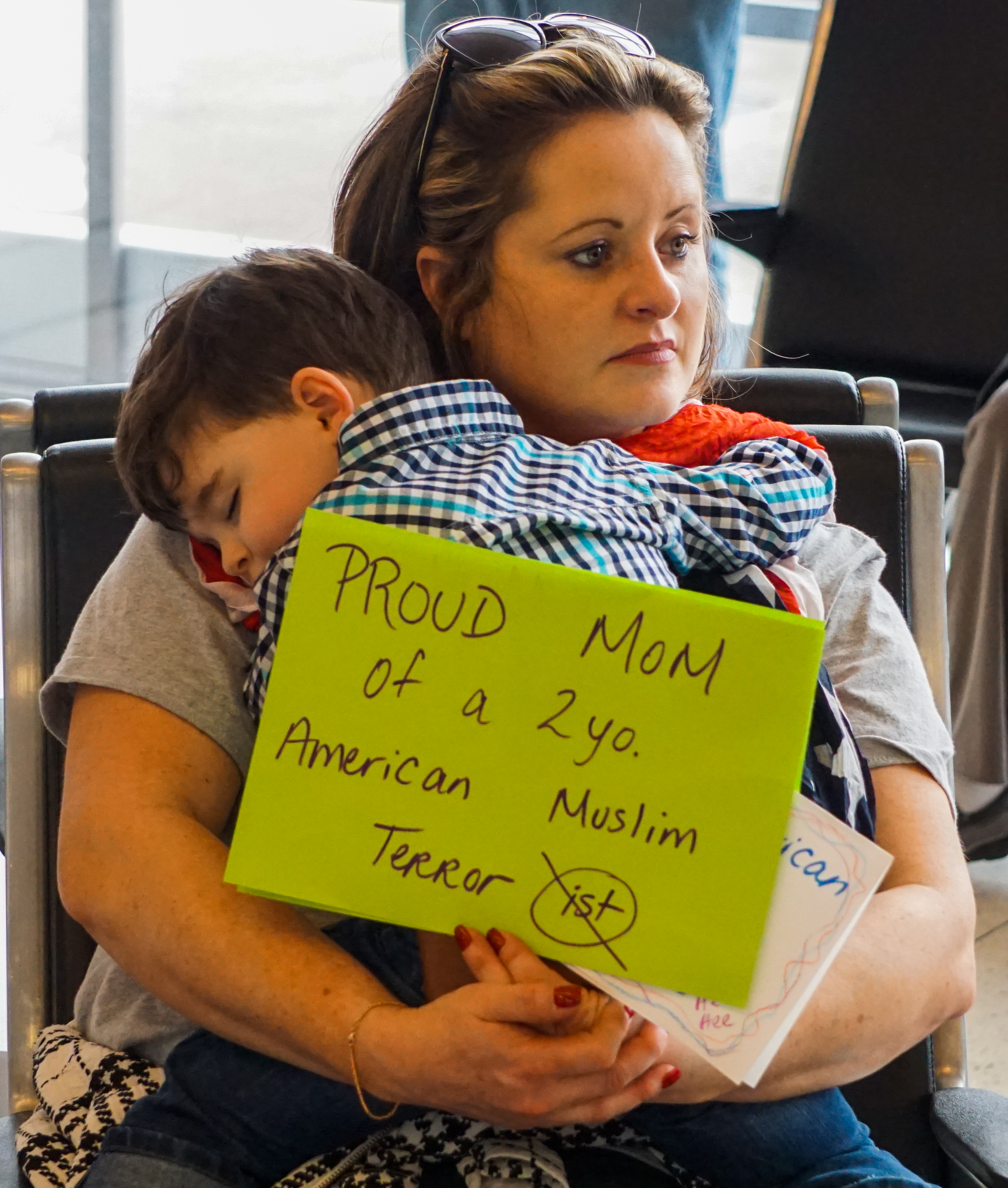 A mother holds her child while at a protest at DFW International Airport. Photo by Josue Hernandez/The Et Cetera