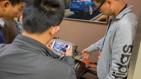 Liu Jun examines a car engine in T building. Photos by Jesus Ayala/The Et Cetera