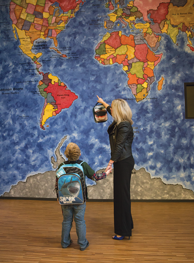 Dumont points out the United States to Ryder on a map mural. Alejandra Rosas/The Et Cetera