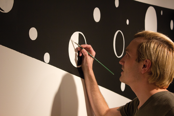 Artist Will Heron paints murals directly onto the walls of the H Gallery to create a unique, temporary piece. Photo by David Sanchez.