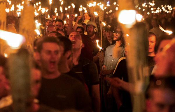 """Neo-Nazis, alt-right and white supremacists march the night before the """"Unite the Right"""" rally, on Friday, Aug. 11 through the University of Virginia in Charlottesville, Va. Photo by Zach D Roberts/NurPhoto/Zuma Press/TNS"""