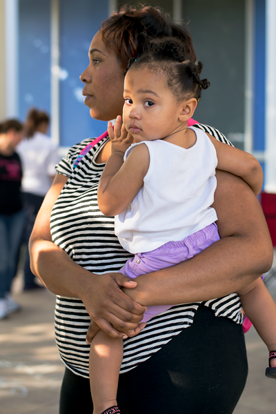 Harvey evacuee Tiffany Howell stands outside the Samuell Grand Recreation Center, turned into a Red Cross shelter, with her 17-month-old daughter Jordan. Howell evacuated from her Southeast Texas apartment before Harvey made landfall, taking her three children and $50 and driving to Dallas. Photo by Dan luna/The Et Cetera