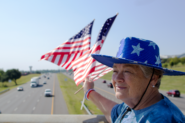 """Karen Winton of Seagoville waves American flags with Tony Cottrell every year. """"This is the day I'll never forget,"""" Winton said. Cottrell has gone to the New Market Road Bridge over Interstate- 635 every Sept. 11 since 2002 to remember the terror attacks in 2001. Photo by Yesenia Alvarado/The Et Cetera"""