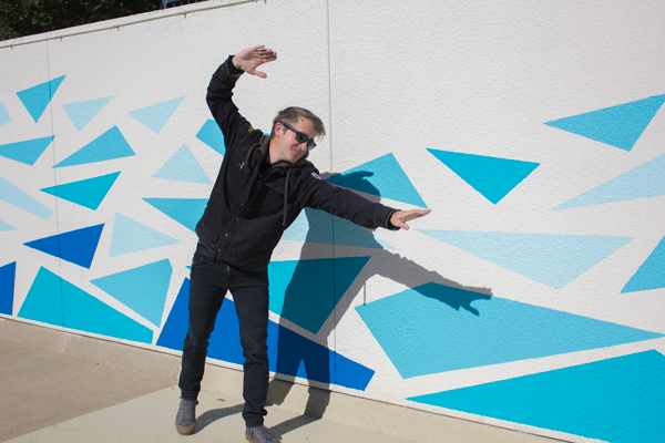 """Brennen Bechtol """"swims"""" beside the mural he painted for the pool. Photo by Macks Prewitt/The Et Cetera"""
