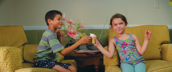 """Scooty, left, and Moonee, played by Christopher Rivera and Brooklynn Prince, share an ice cream during a scene in """"The Florida Project.""""  Courtesy of A24"""