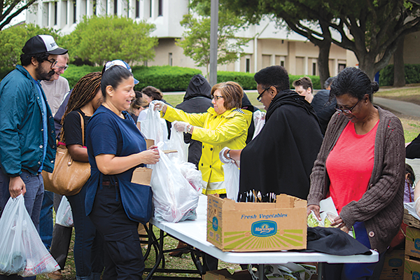 Volunteers hand out fres produce during one of the food truck visits to campus. The Et Cetera file photo.