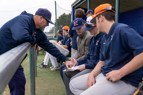 Coach Michael Martin looks over pitching records from practice with some of the team's pitchers. Throwing more strikes is one of Martin's biggest focuses for the team going into conference play. Photo by Yesenia Alvarado/The Et Cetera