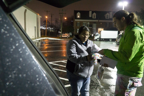 Mayra Fierro and Caleb Bay collect basic necessities from Bay's car to give to someone sleeping in a blue tent under the Genesis Benefit Thrift Store entrance on Feb. 9. Photo by Yesenia Alvarado/The Et Cetera