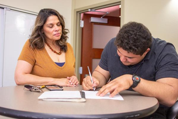 Liz Nichols assists criminal justice major Yonathan Mejia after African American studies class. Photo by Yesenia Alvardo/The Et Cetera