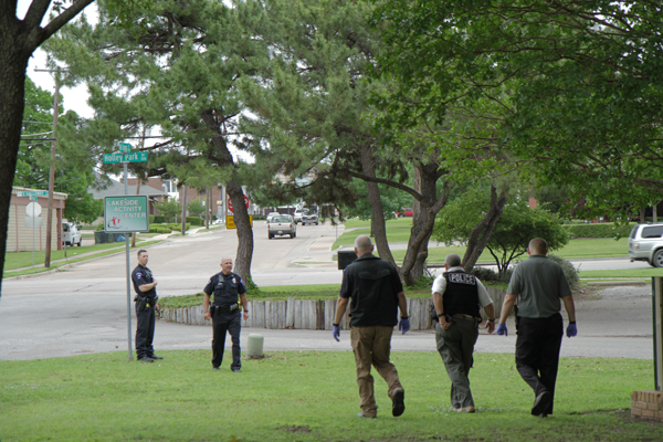 Mesquite police officers search City Lake Park where witnesses saw a group flee after Thursdays shooting. Photo by Anthony Lazon/The Et Cetera