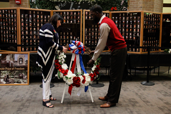 Veteran Tommy Williams and Rachel Wolf, the  associate vice president of academic affairs and student success place a Memorial Day wreath in front of the Veterans Day memorial wall May 6.