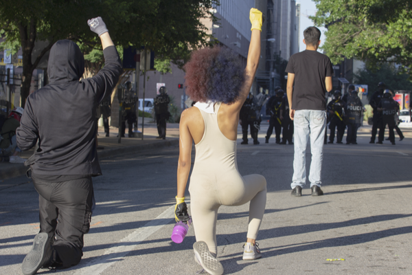 Protesters raise their fists in the air while taking a knee on Jackson Street near South Lamar Street in Dallas on May 30. Photo by Skye Seipp/The Et Cetera