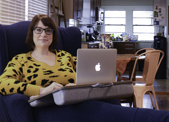 Erica Stephens works from her laptop Feb. 28 at her house, which suffered water damage and a power outage during the recent winter storm. Photo by Chantilette Franklin/The Et Cetera