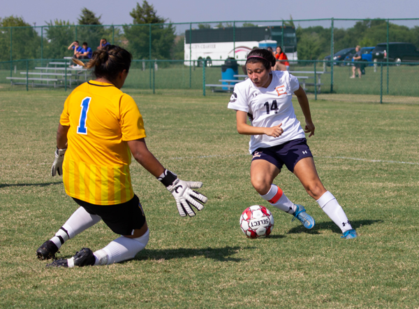 Laisha Garcia dribbles the ball beside the goalie during a game against Jarvis Christian College on Aug. 26. Photo by Rory Moore/The Et Cetera