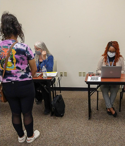 Nancy Abdo, left, helps someone register for the COVID-19 vaccine incentive in C-135 on Sept. 9. Photo by Vera DeJohnette/The Et Cetera